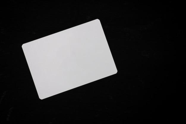 Weißes leeres papier auf einem schwarzen hölzernen schreibtisch Premium Fotos