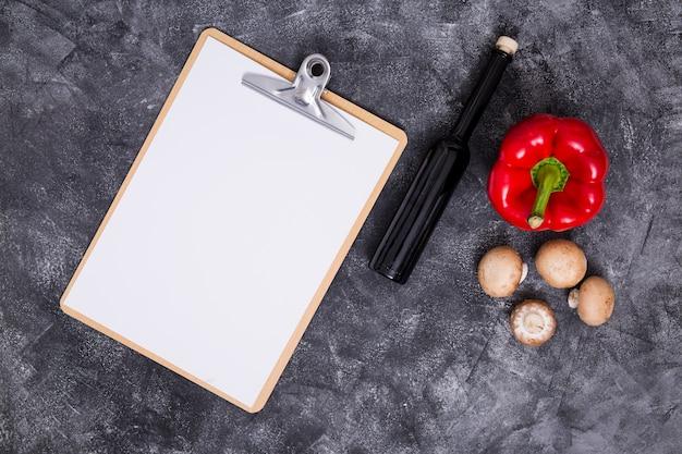 Weißes leeres papier in zwischenablage mit paprika; pilz und flasche auf schwarzem strukturiertem hintergrund Kostenlose Fotos
