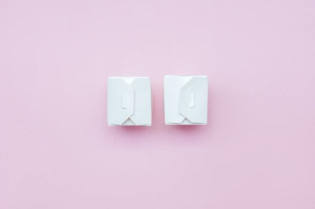 Weißes mitnehmerlebensmittel mit zwei papierkästen auf weißbuchkasten des rosa hintergrundes mit beschneidungspfad Premium Fotos