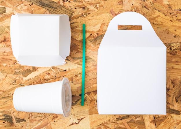 Weißes mitnehmernahrung mit trinkhalm des türkises auf hölzernem hintergrund Kostenlose Fotos