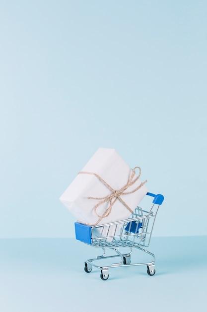 Weißes paket im einkaufswagen auf blauem hintergrund Kostenlose Fotos