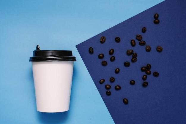 Weißes pappglas mit einem schwarzen plastikdeckel auf einer blauen und cyan-blauen oberfläche mit kaffeebohnen. glas mit kaffee zum mitnehmen. die trendfarbe ist klassisches blau. exemplar, flach zu legen Premium Fotos