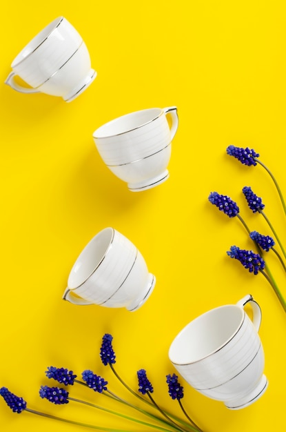 Weißes porzellan-kaffee- oder teeset mit muscariblumen auf gelb Premium Fotos