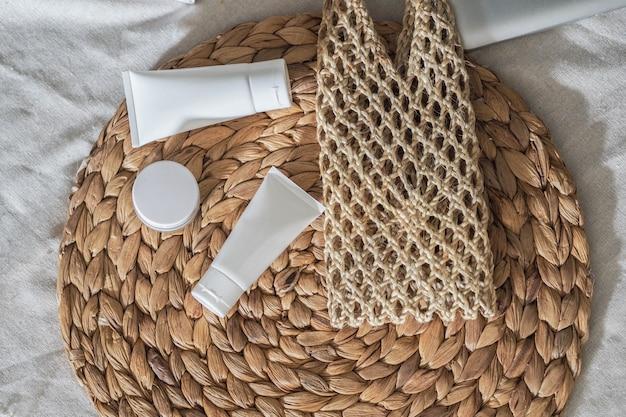 Weißes produkt der kosmetischen flaschenbehälter mit trockener blume und gesponnenen handtaschen. Premium Fotos