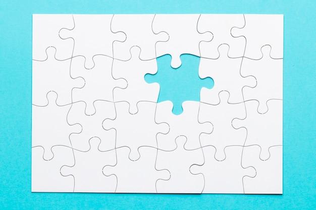 Weißes puzzle mit einem fehlenden stück auf blauem hintergrund Kostenlose Fotos