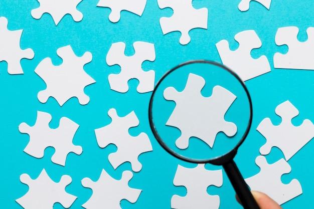 Weißes puzzlestück gesehen durch lupe über blauem weißem hintergrund Kostenlose Fotos