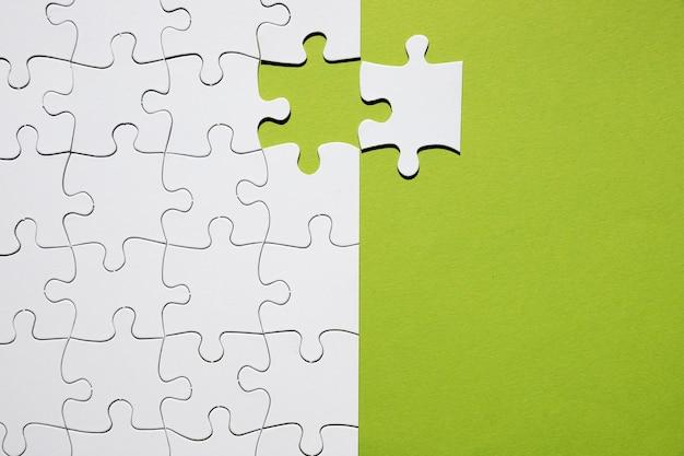 Weißes puzzleteil unterschiedlich mit weißem puzzlespielgitter auf grünem hintergrund Kostenlose Fotos