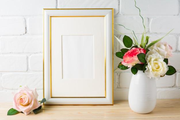 Weißes rahmenmodell auf backsteinmauer mit rosen Premium Fotos