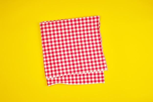 Weißes rotes kariertes geschirrtuch auf einem gelben hintergrund Premium Fotos