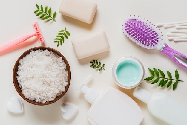 Weißes salz in der schüssel mit kosmetikprodukten und -haarbürste auf weißem hintergrund Kostenlose Fotos