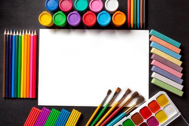 Weißes sauberes albumblatt. hilfsmittel für anstrich und kunst im schwarzen hintergrund. Premium Fotos