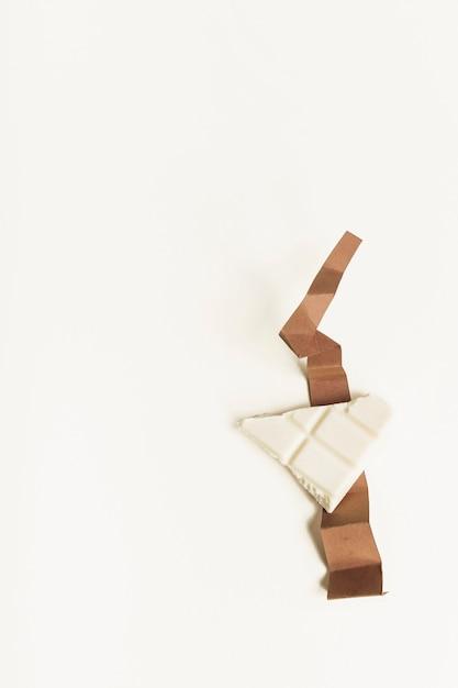 Weißes schokoladenstück auf gefaltetem braunem kartenpapier gegen weißen hintergrund Kostenlose Fotos