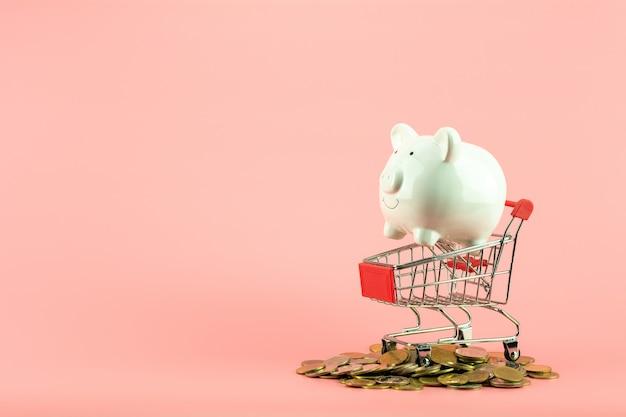 Weißes sparschwein im kleinen warenkorb auf stapel von goldenen münzen. Premium Fotos
