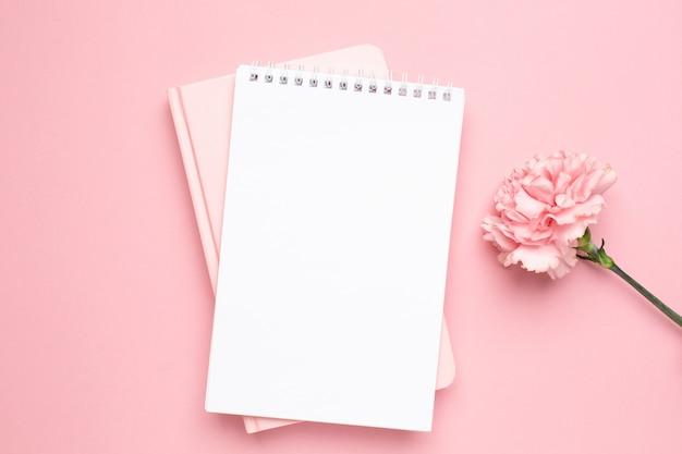 Weißes und rosa notizbuch mit gartennelkenblume auf einem rosa hintergrund Premium Fotos