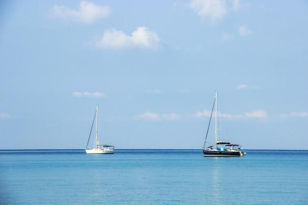 Weißes und schwarzes segelboot des touristen am hintergrund der blaue himmel um haad bangbao von koh kood Premium Fotos