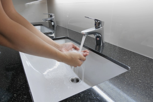 Weißes waschbecken und wasserhahn auf granit-theke mit handwäsche Premium Fotos