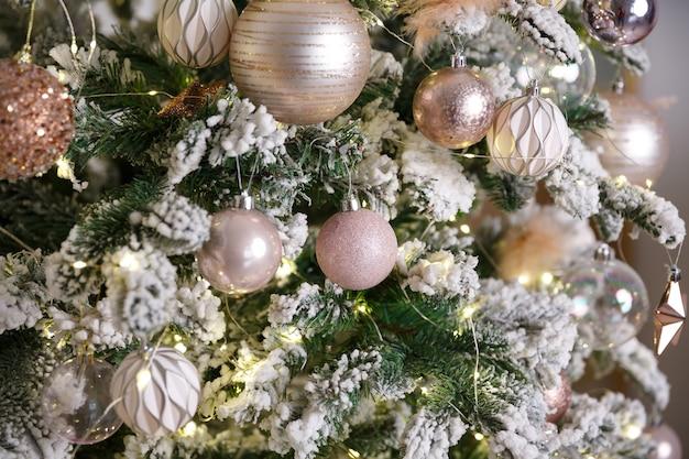Weißes weihnachtsspielzeug, das auf grünem schneebedecktem tannenzweig hängt Premium Fotos