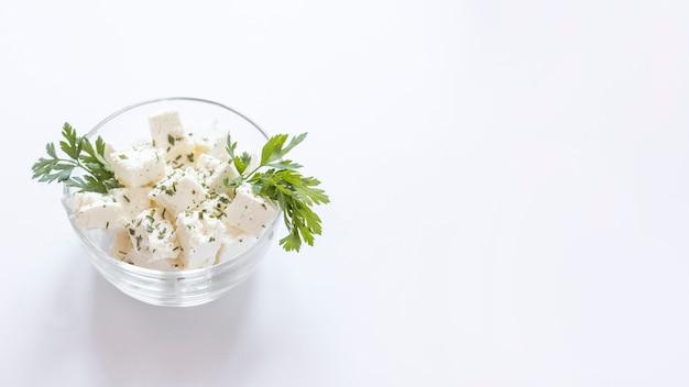 Weißkäsewürfel mit petersilie in der glasschüssel auf weißem hintergrund Kostenlose Fotos