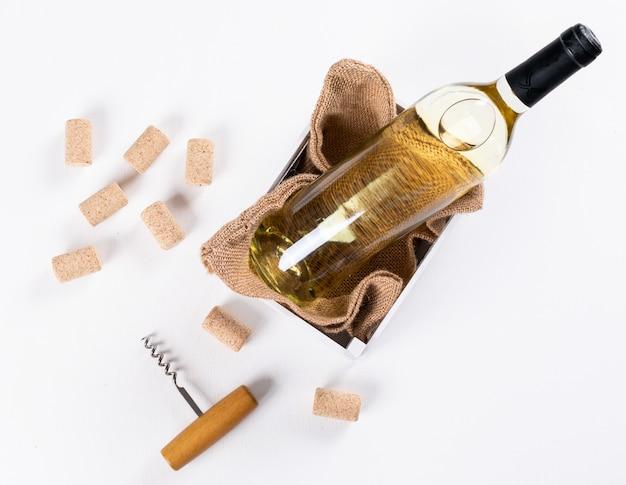 Weißwein der draufsicht in der flasche in der hölzernen kiste und im leinentasche auf der weißen horizontalen Kostenlose Fotos