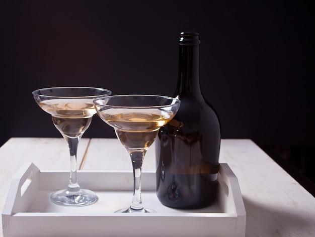 Weißwein in gläsern, flasche auf dem weißen hölzernen behälter Premium Fotos