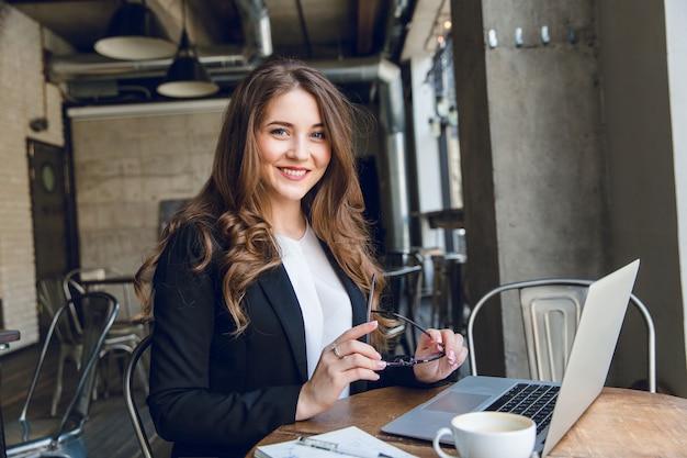 Weit lächelnde geschäftsfrau, die am laptop arbeitet, der in einem café sitzt Kostenlose Fotos