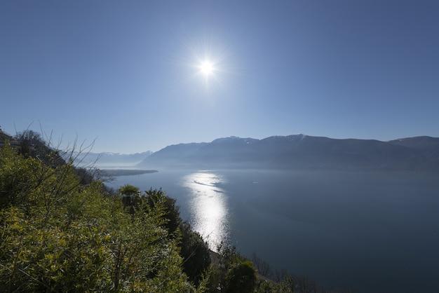 Weitwinkelaufnahme der sonne, die über dem wasser und den bergen scheint Kostenlose Fotos