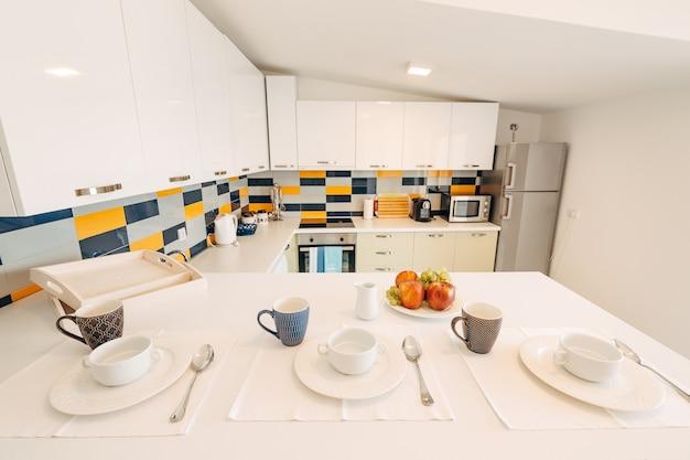 Weitwinkelaufnahme einer küche im weißen stil mit tisch, tassen und früchten für drei personen Premium Fotos