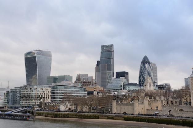 Weitwinkelaufnahme von hohen glasgebäuden in london in der nähe des sees Kostenlose Fotos