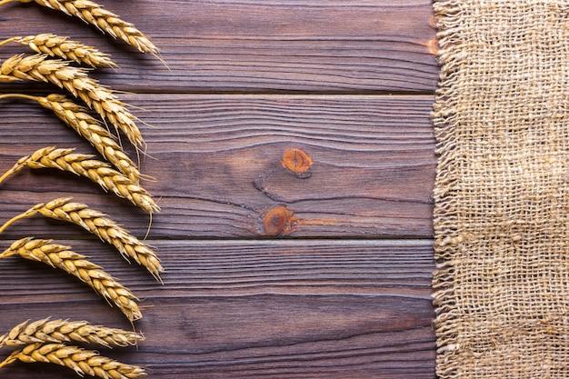 Weizenähren und stoff auf hölzernen hintergrund Premium Fotos