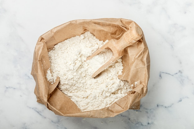 Weizenmehl und eine hölzerne schaufel in einer papiertüte auf einer marmortabelle, bäckereikonzept Premium Fotos