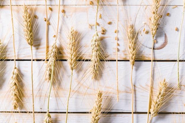 Weizenohren und körner auf holzbrettern Premium Fotos