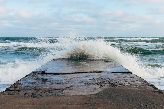 Wellen, die auf einem konkreten pier bei windigem wetter brechen Premium Fotos