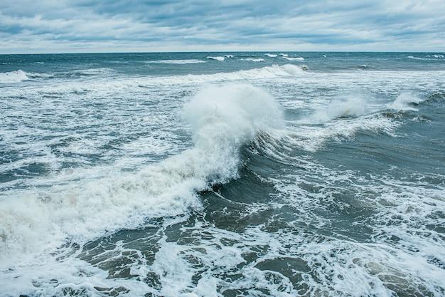 Wellen, die bei hoher see und starken winden brechen und sprühen. stürmen sie in dem meer am bewölkten regnerischen tag des herbstes. Premium Fotos