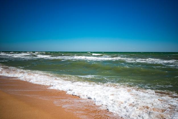 Wellen eines lauten meeres mit blauem wasser, das an einem sonnigen warmen sommertag auf einem sandstrand spritzt Premium Fotos