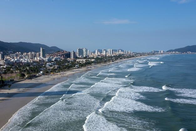 Wellen treffen den strand mit stadt im hintergrund Premium Fotos