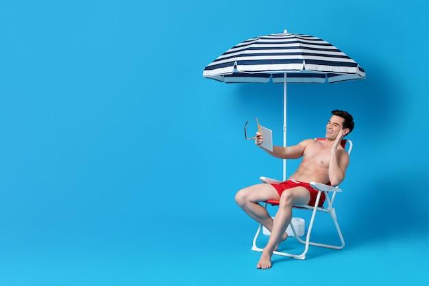Wellenartig bewegende hand des hemdlosen mannes beim videoanruf beim sitzen auf strandstuhl Premium Fotos