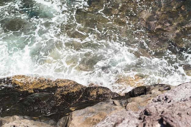 Wellenförmiges wasser der nahaufnahme am strand Kostenlose Fotos