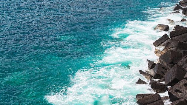 Wellenförmiges wasser der nahaufnahme an der felsigen küste Kostenlose Fotos