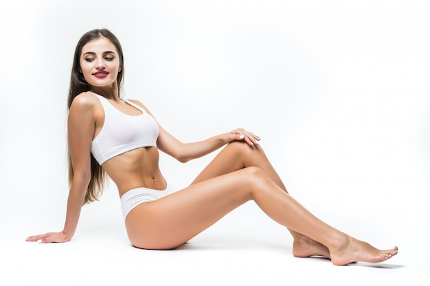 Wellness- und schönheitskonzept. schöne schlanke frau in der weißen unterwäsche, die auf weißem boden sitzt Kostenlose Fotos