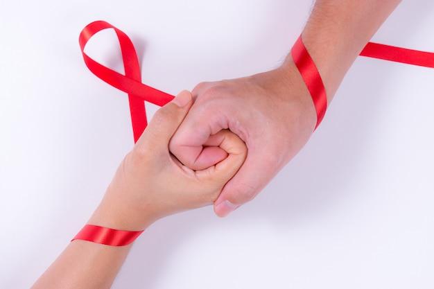 Welt-aids-tag. mann- und frauenhändchenhalten mit rotem band. aids awareness. Premium Fotos