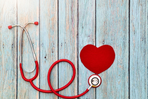 Weltgesundheitstag, gesundheitswesen und medizinisches konzept, rotes stethoskop und rotes herz auf dem blauen hölzernen hintergrund Premium Fotos
