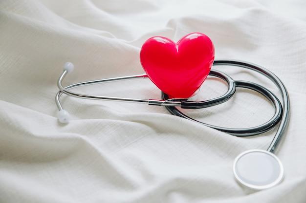 Weltgesundheitstag. rotes herz mit stethoskop auf weißem stoff Premium Fotos