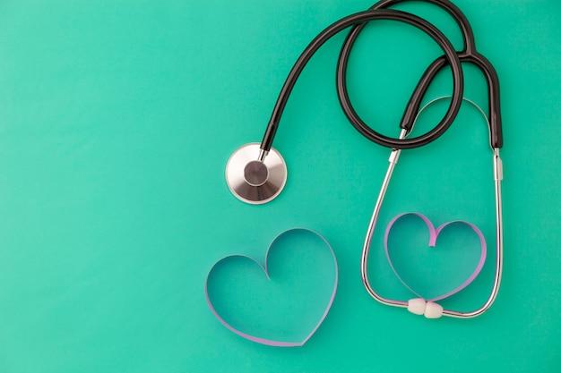Weltgesundheitstaghintergrund, stethoskop und rosa bandherz auf grünem hintergrund, konzeptgesundheitswesen und medizinischem hintergrund Premium Fotos