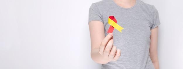 Welthepatitis-tag-konzept. mädchen hält in ihrer hand bewusstseinssymbol rot-gelbes band Premium Fotos