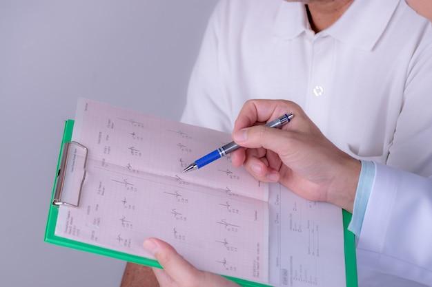 Weltherztag. doktorhände mit kardiogrammdiagramm mit stift. kardiologe, der seine geduldigen ekg-ergebnisse erklärt. Premium Fotos