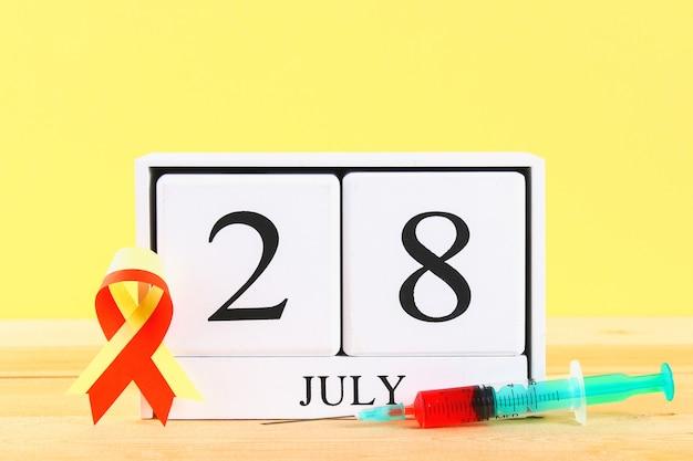 Welttag der hepatitis. ein hölzerner weißer kalender am 28. juni auf einer tabelle gegen eine gelbe wandrückseite Premium Fotos