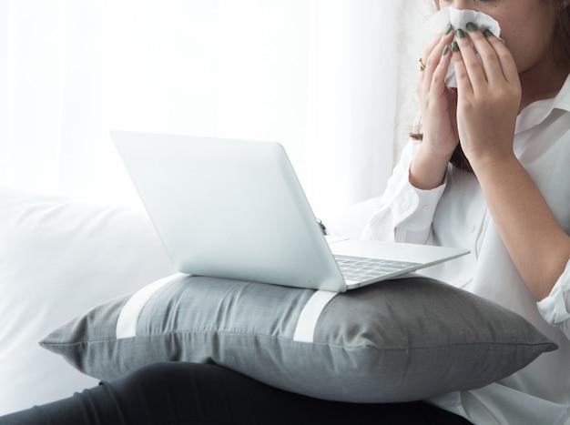 Wenn eine frau fieber hat, niest sie, während sie einen laptop im schlafzimmer benutzt. Premium Fotos