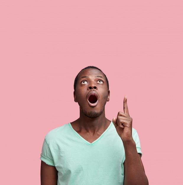 Werbekonzept. erstaunlicher hübscher junger schwarzer mann in freizeitkleidung, zeigt finger auf leere wand mit kopienraum Kostenlose Fotos