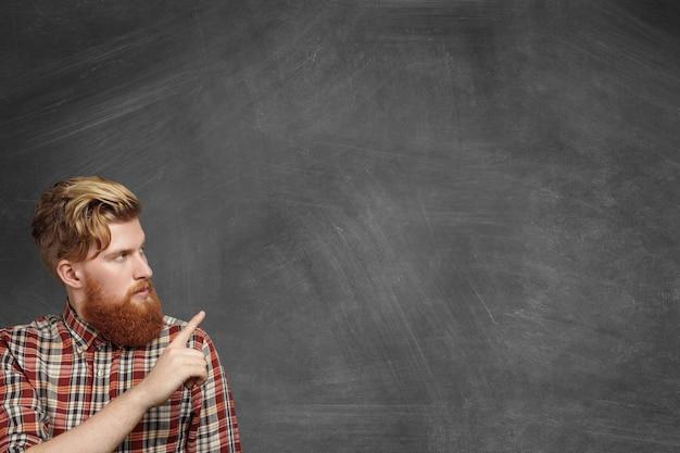 Werbekonzept. hübscher junger bärtiger mann im lässigen karierten hemd, das leere tafel betrachtet und seinen zeigefinger auf kopierraum für ihren text oder werbeinhalt zeigt. Kostenlose Fotos