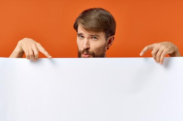 Werbeplakat in den händen eines mannes auf einer orange gestikulierten hand mit seinen händen copy space Premium Fotos